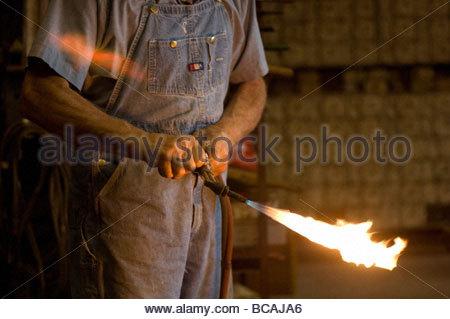 Ein Mann hält einen Schweißbrenner auf seiner Farm in der Nähe von Cortland, Nebraska. - Stockfoto