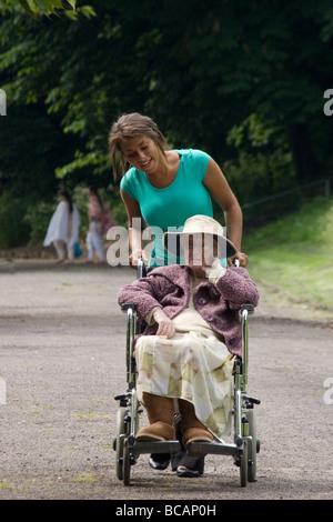 junge Frau drängen ältere Dame im Rollstuhl in den park - Stockfoto