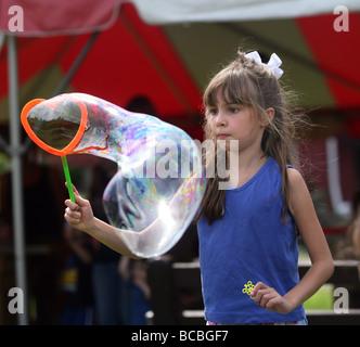 Ein junges Mädchen spielt mit Luftblasen auf einem Shelton Connecticut USA Sommerfestival - Stockfoto