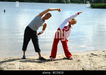 Paar Fitness, körperliche Betätigung in der Nähe von Wasser am Strand, Fitness am Morgen - Stockfoto