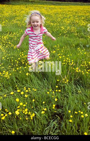 England, West Dorset Forde Abtei. Junges Mädchen läuft durch ein Feld von wilden Butterblumen, angrenzend an den - Stockfoto