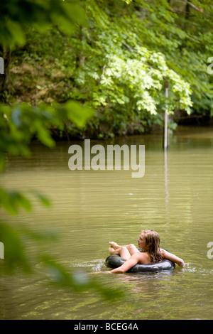 Teenager-Mädchen schwebt auf einem Innertube nahe einem Waldgebiet - Stockfoto