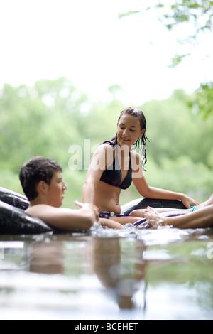 Jugendliche, die Spaß in Innertubes im Wasser - Stockfoto