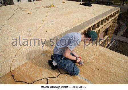 Ein kleiner Junge nimmt sich Sperrholz ein Nebraska-Haus. - Stockfoto