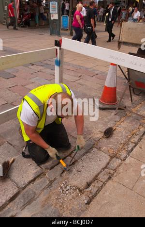 Ein Mann ausbessern das Pflaster in der Innenstadt von Norwich Norfolk Uk - Stockfoto