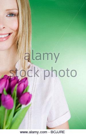 Eine junge Frau hält eine Reihe von violette Tulpen, Lächeln - Stockfoto