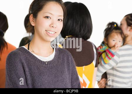 Junge Frau in der Gruppe von Menschen - Stockfoto