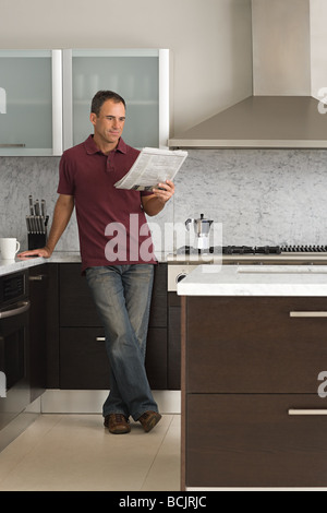 Mann liest eine Zeitung in Küche - Stockfoto