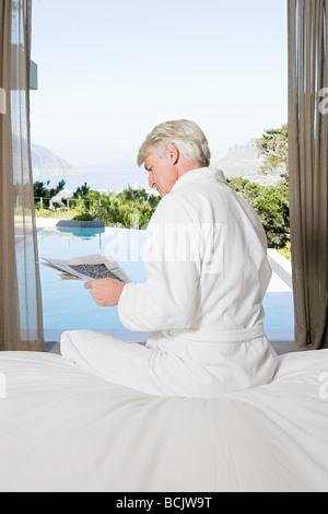 Applying Mann in Robe sitzen im Bett und Las Zeitung mit Blick zum pool - Stockfoto