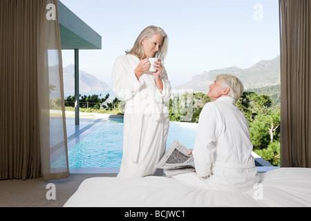Applying paar tragen Badezimmer im Schlafzimmer mit Blick zum pool - Stockfoto