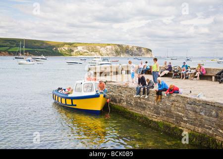 Familien, die Krabben aus der Hafenmauer und ein Boot zum Vergnügungsreisen rund um die Bucht.  Am Meer Stadt Swanage, - Stockfoto
