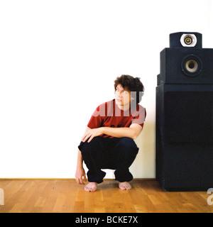 Junger Mann kauert neben Lautsprecher - Stockfoto