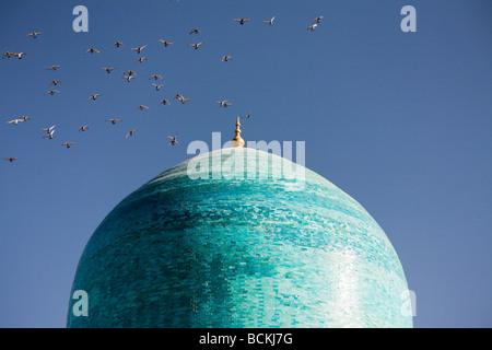 Vogelschwarm fliegt über der Kuppel der Moschee - Stockfoto