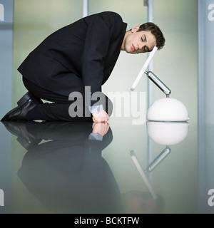 Mann kniet auf Tisch mit Kopf auf dem Bildschirm - Stockfoto