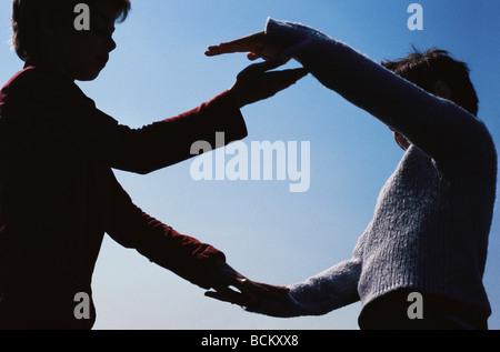Zwei Kinder machen Kreis mit Armen, Silhouette, niedrigen Winkel Ansicht - Stockfoto