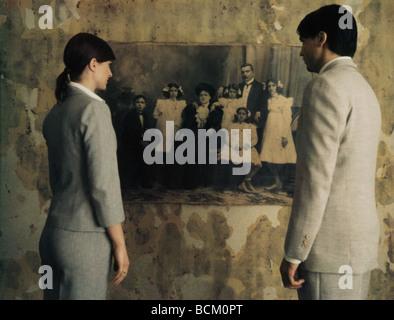 Mann und Frau stehen Seite an Seite mit Blick auf schwarz / weiß Foto an Wand, Rückansicht - Stockfoto