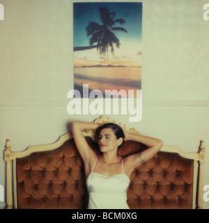 Frau sitzt auf dem Sofa mit Händen hinter dem Kopf und die Augen geschlossen, unter tropischen Foto an Wand - Stockfoto