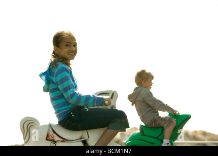 Kinder reiten Schaukelpferde auf Spielplatz, Fokus auf Vordergrund - Stockfoto