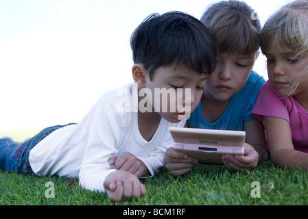 Drei Kinder auf dem Rasen liegen, spielen mit video Spiel, Nahaufnahme - Stockfoto
