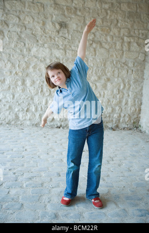 Mädchen mit Down-Syndrom stehen mit Armen angehoben, vorgibt, ein Flugzeug zu sein - Stockfoto