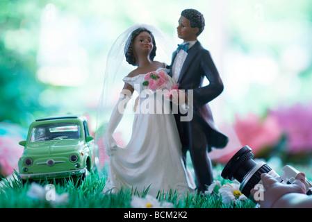 Braut und Bräutigam Figuren posieren im Bereich der Kunstblumen, Hand Holding Kamera im Vordergrund - Stockfoto