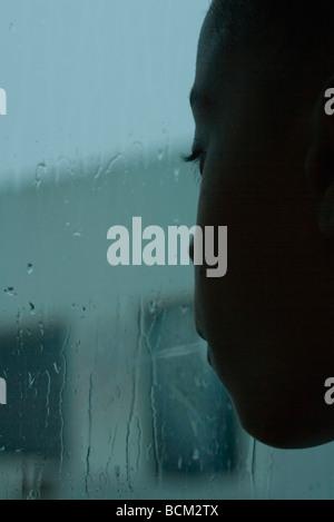 Mädchen suchen Fenster am regnerischen Tag, Nahaufnahme - Stockfoto