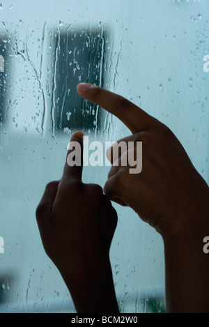 Eltern und Kind Ablaufverfolgung Regentropfen am Fenster mit Fingern, verkürzte Ansicht der Hände - Stockfoto