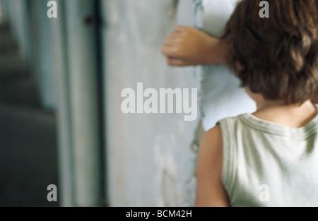 Junge Wand gelehnt, mit Kopf gegen Arm, Rückansicht - Stockfoto