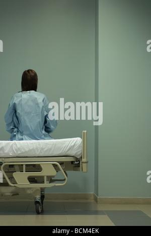 Patientin sitzt am Krankenhausbett, Vormauerschale, Rückansicht - Stockfoto