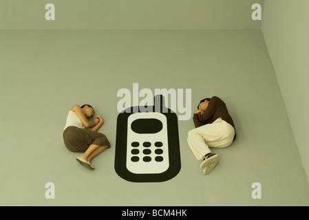 Mann und Frau mit großen Handy-Grafik zwischen ihnen auf dem Boden liegend - Stockfoto
