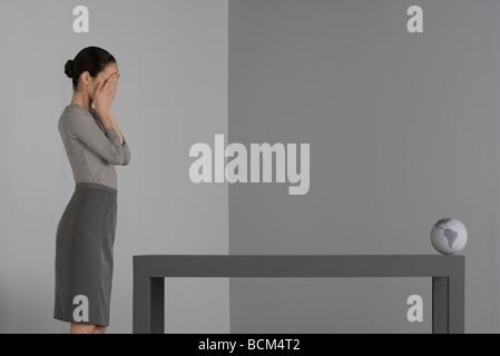 Frau stehend neben Tisch bedeckte Gesicht mit den Händen, Globus, am gegenüberliegenden Ende der Tabelle - Stockfoto