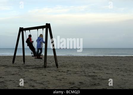 Zwei Kinder auf einer Schaukel beobachten ein Schiff in der Ferne - Stockfoto