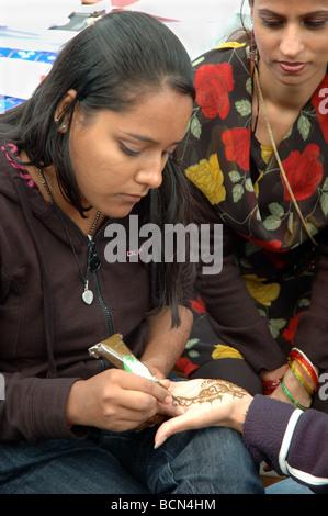 asiatische Frau anwenden Mendi, ein Muster von Henna, während die Leicester Mela, Leicester, England, UK - Stockfoto