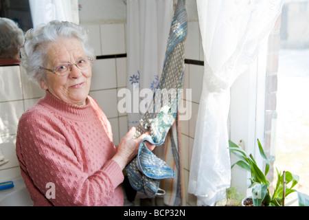 Frau in Ihren Siebzigern Steht in der Küche Und Trocknet Sich sterben Bäckerlehrling ab - Stockfoto