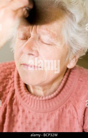 Frau in Ihren Siebzigern feststeht Sitsch Im sich pudern - Stockfoto