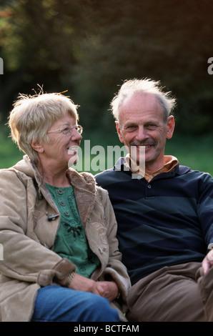 Im Alter von paar in 50 sieht in die Kamera auf Parkbank - Stockfoto