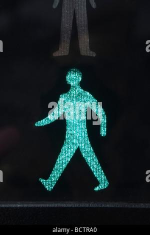 Nahaufnahme von beleuchteten Fuß Grüner Mann sicher zu überqueren Straße Symbol auf einem Fußgängerüberweg Ampel. - Stockfoto
