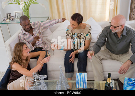 Zwei Männer und zwei Frauen Toasten mit Champagner-Flöten in einer Partei - Stockfoto