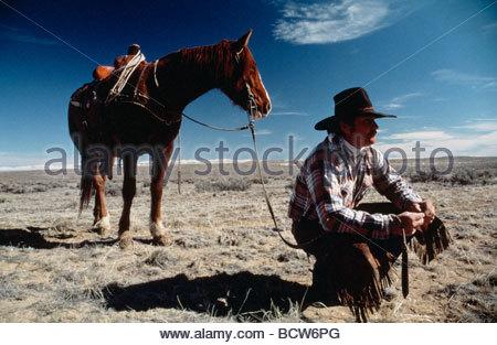 Cowboy auf eine Landschaft mit seinem Pferd kauert - Stockfoto