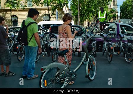 Paris Frankreich, Franzosen, Frau im Kleid, Rückseite, öffentliche, kostenlose Fahrräder, Velib, Parken auf der - Stockfoto