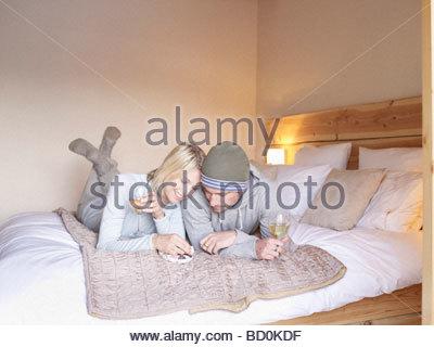 Frau und Mann liegt auf dem Bett Essen - Stockfoto