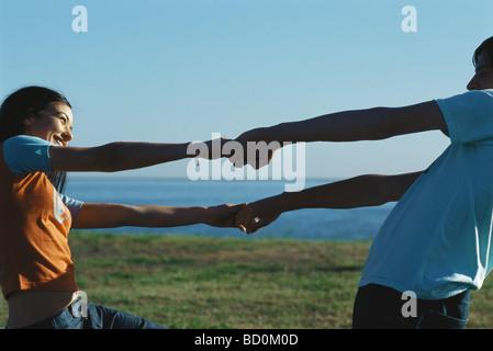 Junges Paar Hand in Hand und lehnte sich zurück lächeln einander gegenüber - Stockfoto