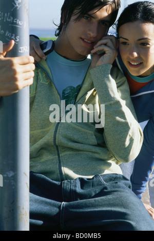Junge Freunde hören Handy zusammen - Stockfoto