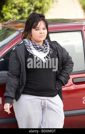 Junge Frau, die neben dem Auto stehend - Stockfoto