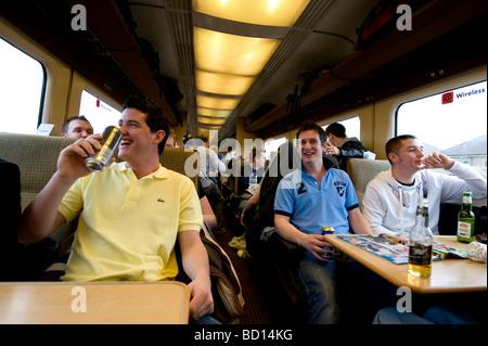 Junge weiße europäische Männer auf einer Zugfahrt zu feiern. - Stockfoto