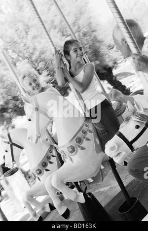 Mädchen reiten Karussell mit ihren Großeltern - Stockfoto