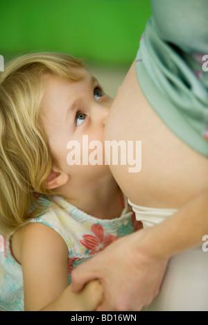 Kleines Mädchen schwangere Mutter Bauch gelehnt - Stockfoto