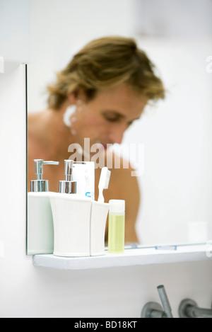 Mann mit Rasierschaum auf Gesicht spiegelt sich im Badezimmerspiegel - Stockfoto