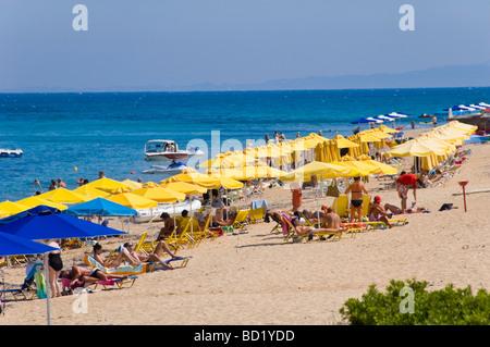 Entspannen Sie sich auf Liegestühlen unter Sonnenschirmen am Sandstrand an der Skala auf der griechischen Insel - Stockfoto