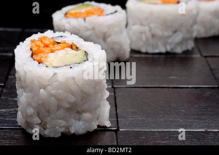 einer horizontalen flachen Fokus Makro Sushi auf einem schwarzen Hintergrund aus Holz - Stockfoto